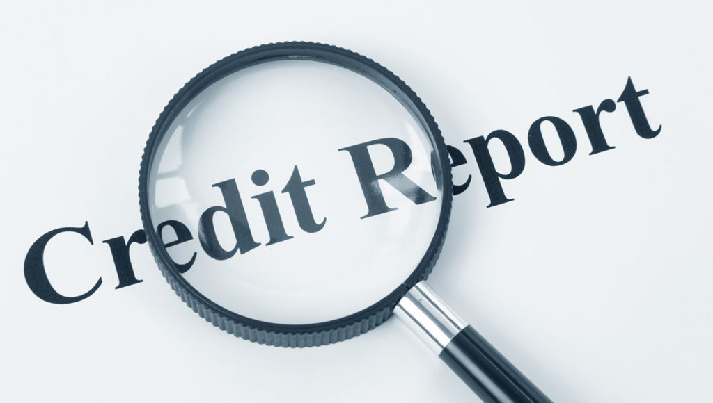 magifying glass inspecting credit report